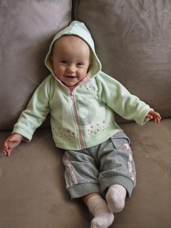 On the sofa stock photo, Little caucasian baby girl sitting on a sofa. by Mariusz Jurgielewicz