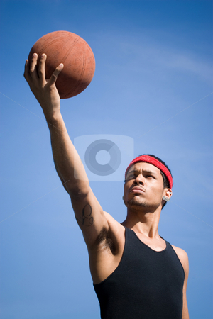 Basketball Player stock photo, A young basketball player holding the ball up to the sky. by Todd Arena
