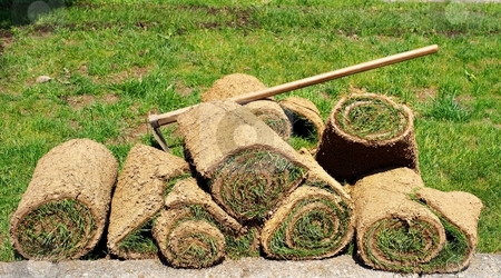 Rolls of grass with a hoe stock photo, Rolls of green grass with a hoe by Juraj Kovacik