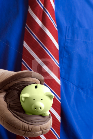 Piggy Bank stock photo, Concept image of a hot investment featuring a closeup view of a piggy bank being held by a pair of oven mitts by Richard Nelson