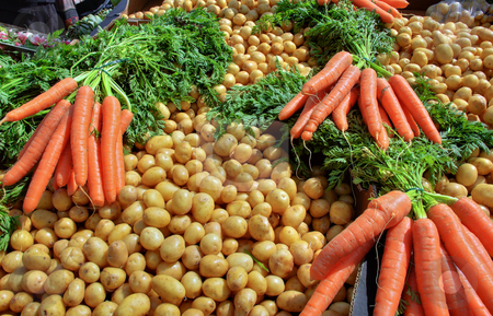 Carrots and Potatoes stock photo, Fresh carrots and Potatoes on a market stall by Robert Ford
