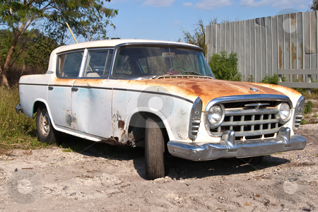 Rusty Old Car stock photo, 1957 car sitting outside a Florida junk yard waiting for someone to buy, then restore it. by Steve Carroll