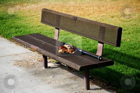 Bench with sports equipment stock photo, Lonely metal bench with a baseball glove and mitt on it by Stacy Barnett