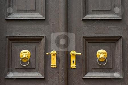 Door knob stock photo, Decorative door knob on old wooden brown doors by Juraj Kovacik