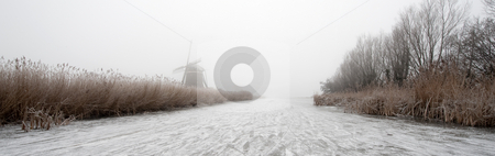 Dutch Winter Panorama stock photo, The archetypal Dutch winter on a foggy morning on a frozen canal surrounded by reed, willows, windmills and a handful of ice skaters approaching in the distance by Corepics VOF