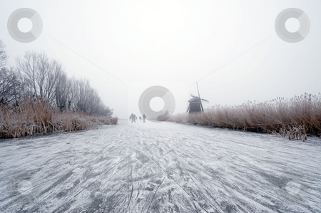 Dutch winter stock photo, The archetypal Dutch winter on a foggy morning on a frozen canal surrounded by reed, willows, windmills and a handful of ice skaters approaching in the distance by Corepics VOF