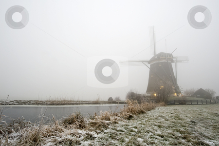 Windmill on a foggy winter morning stock photo, A typical Dutch windmill on a foggy winter morning with ice covered canals, and a frozen dyke by Corepics VOF