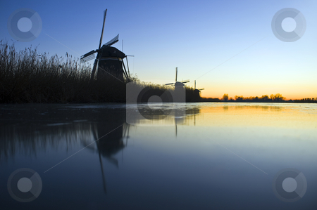 Thee windmills in Wintertime stock photo, Three windmills near an ice covered frozen canal during a winter dawn in Leidschendam, the Netherlands by Corepics VOF