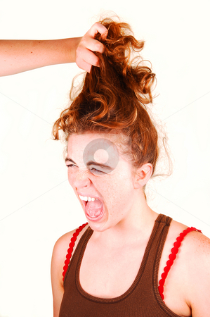 Don't pull my hair. stock photo, Young woman is screaming when another girl is pulling her red hair up. by Horst Petzold