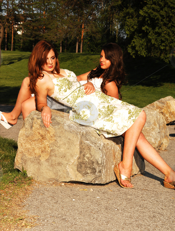 Sisters in the park. stock photo, Two sisters lying on a big rock with there nice dresses and bright red hair in sunset in the park and enjoy the warm weather. by Horst Petzold