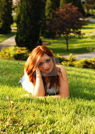 Red haired beauty. stock photo, Beautiful red haired girl lying on the grass in an park and enjoying the gorgeous sunset. by Horst Petzold