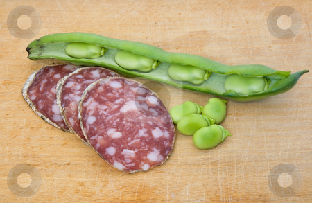 Salami slices and fava  stock photo, Three salami slices with fava beans on a wood chopping board by ANTONIO SCARPI