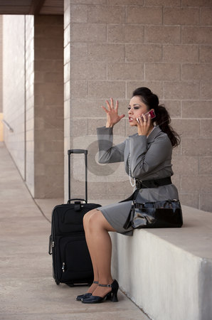 Angry Hispanic Woman Traveler Talking on Cell Phone stock photo, Pretty young angry Hispanic woman with roller suitcase talking on cell phone by Scott Griessel