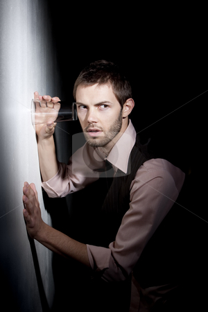 Handsome young man using glass to eavesdrop stock photo, Handsome young man using glass against wall to eavesdrop by Scott Griessel