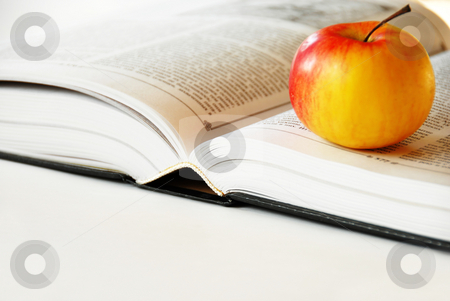 Opened book stock photo, Large opened book with ripe red yellow apple by Julija Sapic