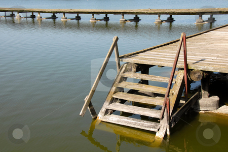 Downstairs into water stock photo, Old wooden stairs on yellowish lake at Palic, Serbia by Julija Sapic