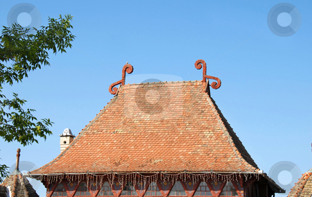 High Tiled Roof stock photo, High tiled roof with decorations over blue sky by Julija Sapic