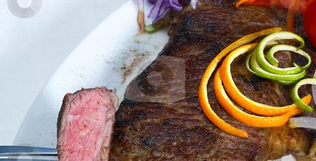 Beef ribeye steak stock photo, Sliced fresh juicy beef ribeye steak grilled with orange and lemon peel on top and vegetables beside by Francesco Perre