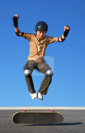 Boy Jumping High from Skateboard stock photo, Boy with protective gear jumping high from a skateboard with blue background. by Denis Radovanovic