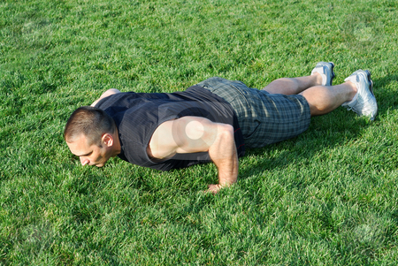 Push Ups On Grass stock photo, Male athlete doing push ups on the grass on a sunny afternoon. by Denis Radovanovic