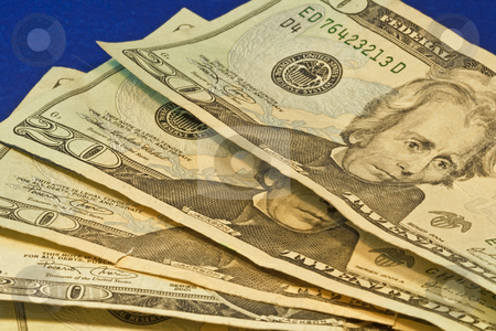 Twenty Dollar Bills stock photo, Stack of twenty dollar bills on blue background by Dennis Crumrin