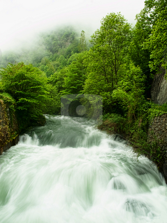 Mountain stream stock photo, Slow motion powerful mountain stream with fog on the top by Laurent Dambies