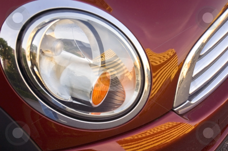 The red driver's side headlight displays a futuristic design. stock photo, A close-up of a futuristic automobile headlight, red bumper, and shiny grille. by Alan G