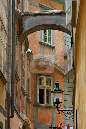Lamp in narrow street stock photo, Old narrow street in a town with lamp by Juraj Kovacik