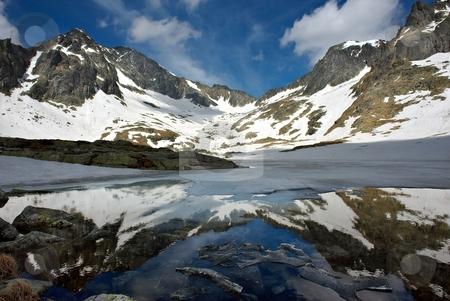 Mountain lake, melting in spring stock photo, Melting lake among mountains with snow and mountains reflection by Juraj Kovacik