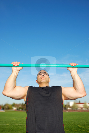 Pull Ups stock photo, Strong man doing pull ups on a bar in a field with blue sky in the background. by Denis Radovanovic