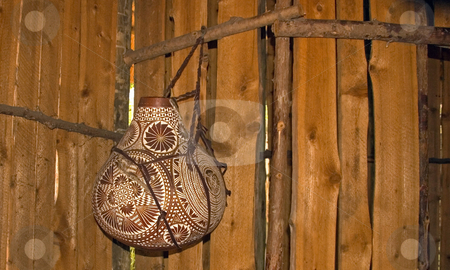 African Style Pottery Hanging stock photo, This African styled pottery is hanging with its intricate designs in a wooden room. by Valerie Garner