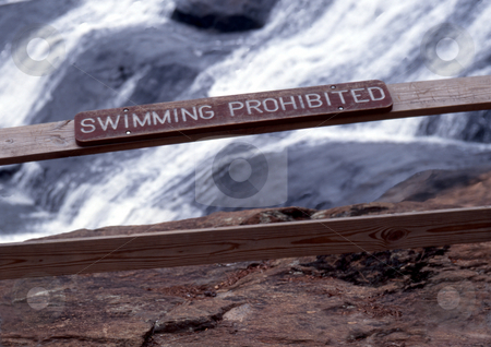 Swimming Prohibited stock photo, Railing with sign with falls in background by Roger Otto