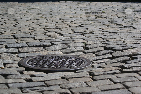 Manhole Cover stock photo, Manhole cover on a cobblestone street in DUMBO, Brooklyn. by Daniel Rosner