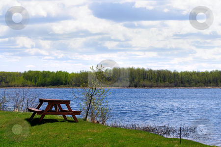 Vacation stock photo, Vacation location in Manitoba, Canada with a small lake and a picnic bench on a partly cloudy day by Richard Nelson