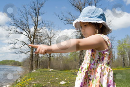 Child Pointing At The Beach stock photo, Four year old girl is at a small beach and pointing at the water by Richard Nelson