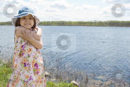 Child At The Lake stock photo, 4 year old girl is smiling and standing in front of a small lake during the summer by Richard Nelson