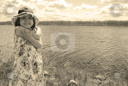 Child At The Lake stock photo, 4 year old girl is smiling and standing in front of a small lake during the summer - processed in a brown tone - not in camera by Richard Nelson