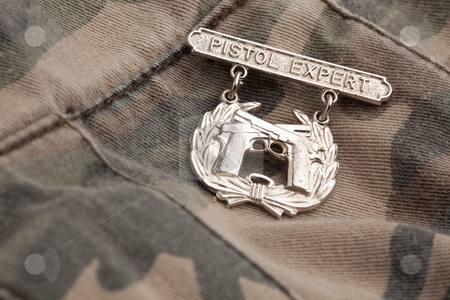Pistol Expert War Medal stock photo, Pistol Expert War Medal on a Camouflage Background. by Andy Dean