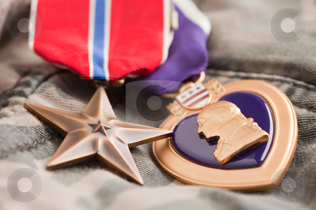 Bronze and Purple Heart Medals on Camouflage Material stock photo, Bronze and Purple Heart Medals on Camouflage Material by Andy Dean