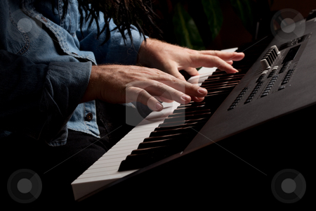 Male Pianist Performs on the Piano Keyboard stock photo, Male Pianist Performs on the Piano Keyboard with Dramatic Lighting. by Andy Dean