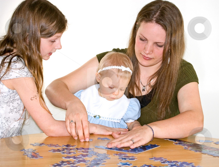 Mom and Two Girls Doing Jigsaw Puzzle stock photo, This mom and 2 girls are putting together a jigsaw puzzle on a table for family time. by Valerie Garner