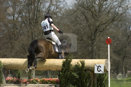 Jumping a trunk stock photo, Eventing rider jumping over an obstacle by Andreas Brenner