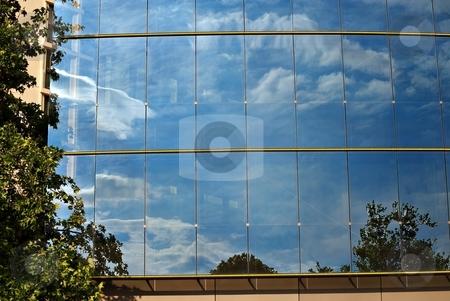 Sky on glass stock photo, Sky reflection with clouds on a facade of modern building by Juraj Kovacik