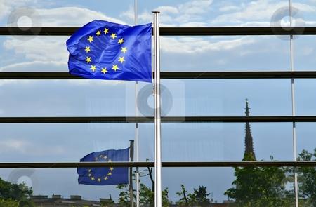 European union flag stock photo, European flag ahead of a glass facade in Vienna by Juraj Kovacik