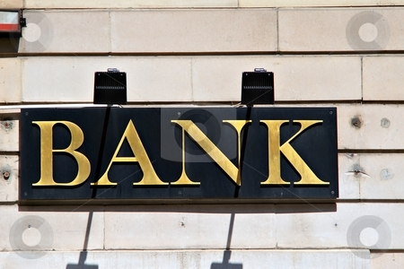 Bank sign stock photo, Metal bank sign on black and slightly obsolete facade by Juraj Kovacik
