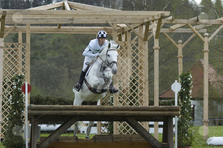 Eventing stock photo, Eventing rider jumping an obstacle on a white horse by Andreas Brenner
