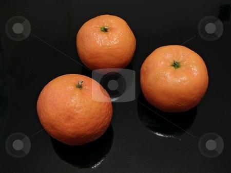 Three mandarines stock photo, Three orange mandarines against the black background by Sergej Razvodovskij