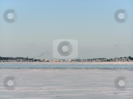 winter landscape stock photo, Tranquil winter lake skyline with the blue sky and town by Sergej Razvodovskij