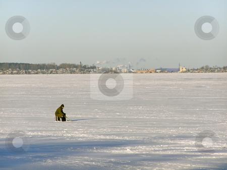 Winter fisherman stock photo, Lonely fisherman on the lake ice far away from town by Sergej Razvodovskij
