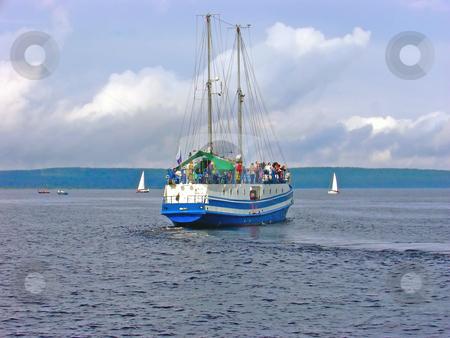 Voyage stock photo, Yacht with passengers against the coastline by Sergej Razvodovskij